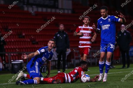 Stock Image of James Wilson (5) of Ipswich Town fouls Fejiri Okenabirhie (9) of Doncaster Rovers