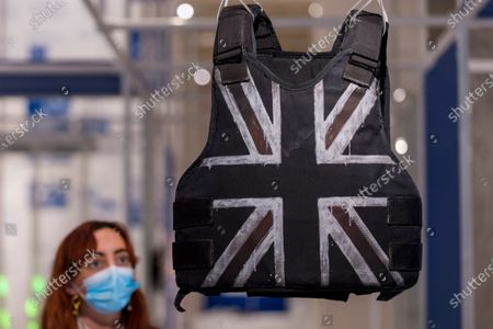 """A staff member views """"Stormzy's stab-proof vest"""", by Banksy, worn by singer Stormzy as the first Black British artist to headline the Pyramid stage at Glastonbury. Preview of the Beazley Designs of the Year at the Design Museum in Kensington. The most innovative designs from January 2019 to the moment the COVID-19 pandemic took hold are on display 21 October to 28 March 2021."""