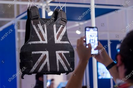 """A person photographs views """"Stormzy's stab-proof vest"""", by Banksy, worn by singer Stormzy as the first Black British artist to headline the Pyramid stage at Glastonbury. Preview of the Beazley Designs of the Year at the Design Museum in Kensington. The most innovative designs from January 2019 to the moment the COVID-19 pandemic took hold are on display 21 October to 28 March 2021."""