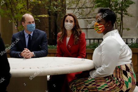Prince William and Catherine Duchess of Cambridge meet pharmacist Joyce Duah as they visit St. Bartholomew's Hospital in London, to mark the launch of the nationwide 'Hold Still' community photography project, Tuesday, Oct. 20, 2020.