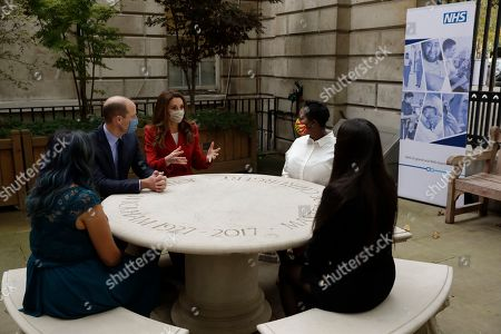 Prince William and Catherine Duchess of Cambridge meet pharmacist Joyce Duah, second right, and pharmacy technicians Amelia Chowdhury, right, and Dipal Samuel, left, as they visit St. Bartholomew's Hospital in London, to mark the launch of the nationwide 'Hold Still' community photography project, Tuesday, Oct. 20, 2020.