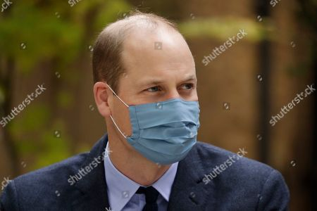 Wearing a face covering to curb the spread of coronavirus Britain's Prince William meets pharmacist Joyce Duah as he visits St. Bartholomew's Hospital in London, to mark the launch of the nationwide 'Hold Still' community photography project