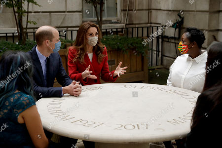 Britain's Prince William and his wife Catherine Duchess of Cambridge meet pharmacist Joyce Duah, second right, and pharmacy technicians Amelia Chowdhury, right, and Dipal Samuel, left, as they visit St. Bartholomew's Hospital in London, to mark the launch of the nationwide 'Hold Still' community photography project
