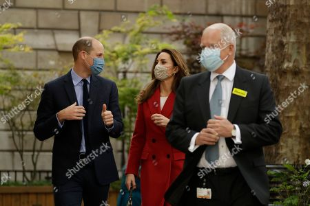 Britain's Prince William and his wife Catherine Duchess of Cambridge walk with Professor Charles Knight the chief executive of St Bartholomew's Hospital, in London, as they visit to mark the launch of the nationwide 'Hold Still' community photography project