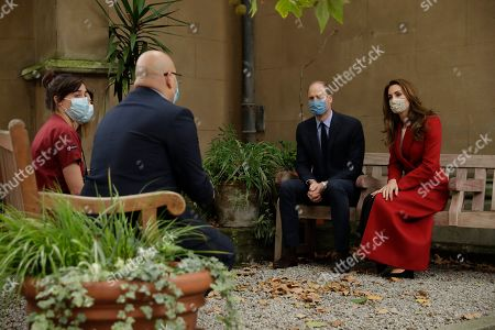 Britain's Prince William and his wife Catherine Duchess of Cambridge meet medical staff, Head of Pharmacy Sotiris Antoniou, third right, Respiratory Physio Isobel Fale, left, and Medical Oncology Trainee and Chief Registrar Dr Myria Galazi, second left obscured at back, as they visit St. Bartholomew's Hospital in London, to mark the launch of the nationwide 'Hold Still' community photography project