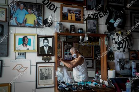 The barber Joao Araujo 'Didi' cuts a client's hair at his barbershop in the city of Santos, Sao Paulo state, Brazil, 10 October 2020 (issued 20 October 2020). The walls of this small venue located a few meters from the Vila Belmiro stadium are full of photographs, paintings and press clippings of the soccer legend Pele. Its owner is known as 'Didi', Pele's exclusive hairdresser since 1956. At 82 years old, Joao Araujo is a celebrity in the city of Santos. His scissors are the only ones that cut the hair of Edson Arantes do Nascimento, known as Pele, considered the best soccer player in history, his most loyal client.