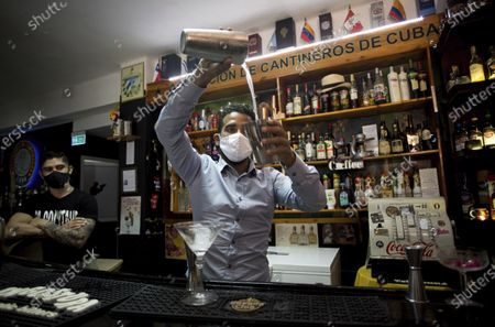 """Wearing masks as a precaution amid the spread of the new coronavirus, bartender Dagoberto Jesus Morejon prepares a cocktail using plants endemic to Cuba, as his business partner Manuel Alejandro Valdes stands behind in Havana, Cuba, . The 26-year-olds have created two drinks called """"Exotic Island"""" and """"Autóctono"""" which have won them recognition and prizes in international competitions"""