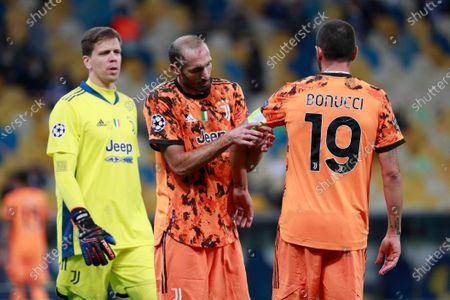 Juventus' Giorgio Chiellini, center, adjusts the captain's hand band on Juventus' Leonardo Bonucci during the Champions League, group G, soccer match between Dynamo Kyiv and Juventus at the Olimpiyskiy Stadium in Kyiv, Ukraine