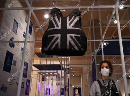 A museum employee poses next to a customised stab-proof vest, designed by street artist Banksy and worn by British musician Stormzy during his performance at the Glastonbury Festival in 2019, during a preview of the 'Beazley Designs of the Year' exhibition at the Design Museum in London, Britain, 20 October 2020.
