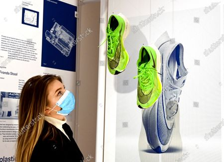 A museum employee poses next to a pair of Nike ZoomX Vaporfly NEXT% running shoes, a prototype version of which the shoes worn by Kenyan long-distance runner Eliud Kipchoge when he ran the Vienna Marathon in October 2019 in under two hours, during a preview of the 'Beazley Designs of the Year' exhibition at the Design Museum in London, Britain, 20 October 2020.