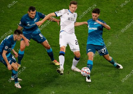 Zenit's Magomed Ozdoev, right, Dejan Lovren, second from left, and Vyacheslav Karavaev, left, fight for the ball with Brugge's Hans Vanaken during the Champions League group F soccer match between Zenit St.Petersburg and Brugge at the Saint Petersburg stadium in St. Petersburg, Russia