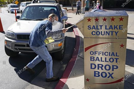Chris Tapscott inserts his ballot in a ballot drop box, in Salt Lake City