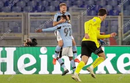 Lazio's Jean-Daniel Akpa Akpro, bottom, celebrates with his teammate Ciro Immobile after scoring his side's third goal during the Champions League group F soccer match between Lazio and Borussia Dortmund at the Olympic stadium in Rome