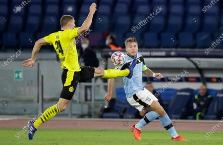 Dortmund's Thomas Meunier, left, challenges for the ball with Lazio's Ciro Immobile during the Champions League group F soccer match between Lazio and Borussia Dortmund at the Olympic stadium in Rome