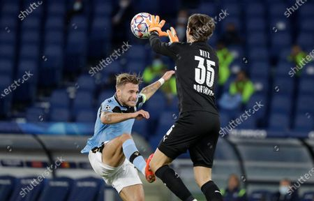 Dortmund's goalkeeper Marwin Hitz, right, saves on Lazio's Ciro Immobile during the Champions League group F soccer match between Lazio and Borussia Dortmund at the Olympic stadium in Rome