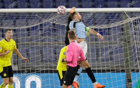Dortmund's goalkeeper Marwin Hitz, top, jumps for the ball with Lazio's Ciro Immobile during the Champions League group F soccer match between Lazio and Borussia Dortmund at the Olympic stadium in Rome