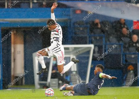 Manchester United's Marcus Rashford leaps over a challenge by PSG's Presnel Kimpembe during the Champions League group H soccer match between Paris Saint-Germain and Manchester United at the Parc des Princes in Paris, France