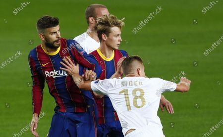 Ferencvaros' David Siger, right, pushes Barcelona's Gerard Pique during the Champions League group G soccer match between FC Barcelona and Ferencvaros at the Camp Nou stadium in Barcelona, Spain