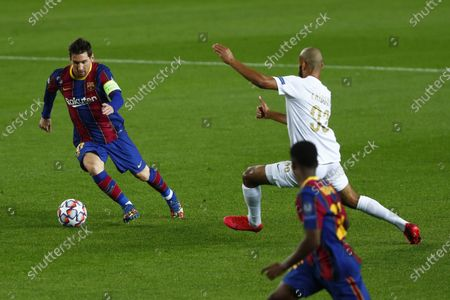 Barcelona's Lionel Messi, left, controls the ball during the Champions League group G soccer match between FC Barcelona and Ferencvaros at the Camp Nou stadium in Barcelona, Spain
