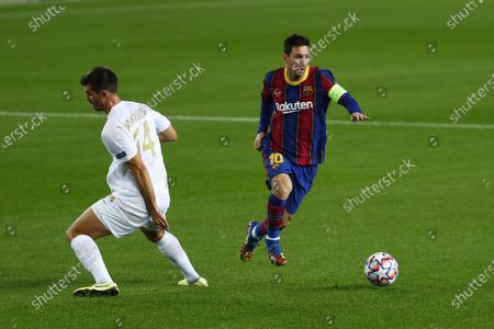 Barcelona's Lionel Messi, right, controls the ball during the Champions League group G soccer match between FC Barcelona and Ferencvaros at the Camp Nou stadium in Barcelona, Spain