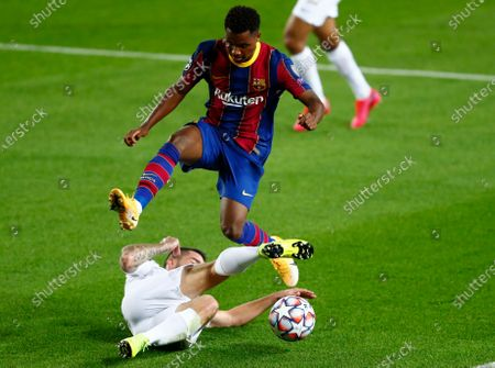 Ferencvaros' Endre Botka, bottom, tries to stop Barcelona's Ansu Fati during the Champions League group G soccer match between FC Barcelona and Ferencvaros at the Camp Nou stadium in Barcelona, Spain