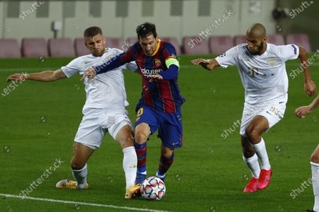 Barcelona's Lionel Messi, center, controls the ball during the Champions League group G soccer match between FC Barcelona and Ferencvaros at the Camp Nou stadium in Barcelona, Spain