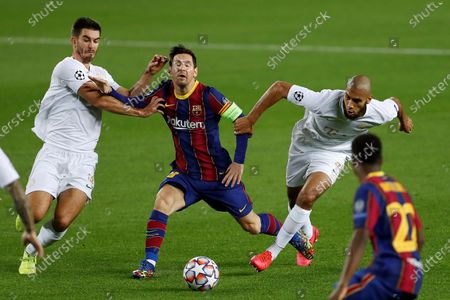 FC Barcelona's Lionel Messi (C) in action against Ferencvaros' midfielders Aissa Laidouni (L) and Ihor Kharatin (R) during the UEFA Champions League Group G soccer match between FC Barcelona and Ferencvaros held at Camp Nou stadium, in Barcelona, Spain, 20 October 2020.