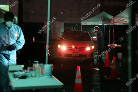 Actors rehearse for 5711 Avalon, a Slauson Rec. Theater Company play that explores a drive through COVID-19 testing site in South Los Angeles on Thursday, Oct. 1, 2020 in Los Angeles, CA. Audience members will watch the play from their cars. (Dania Maxwell / Los Angeles Times)