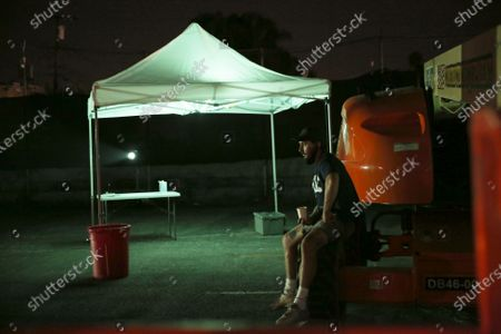 Shia LaBeouf sits on the side during a rehearsal for 5711 Avalon, a Slauson Rec. Theater Company play that explores a drive through COVID-19 testing site in South Los Angeles on Thursday, Oct. 1, 2020 in Los Angeles, CA. LeBeouf, Bobby Soto and Donte Johnson founded the Slauson Rec. Theater Company. (Dania Maxwell / Los Angeles Times)