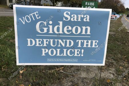 """Sign paid for by the Maine Republican Party that declares """"Vote Sara Gideon/DEFUND THE POLICE!"""" stands along a road, in Portland, Maine. Gideon, a Democrat, is challenging Republican Sen. Susan Collins in the Nov. 3, general election. The Maine Republican Party executive director said the party wanted to highlight Gideon's connections to liberal groups that support defunding police. Gideon said she doesn't support defunding police"""