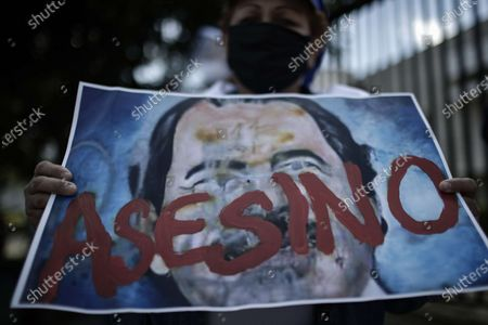 A woman shows a poster with the image of the Nicaraguan President, Daniel Ortega, and the word 'murderer' during a demonstration of Nicaraguans living in Costa Rica who reject the Government of Nicaragua, outside the facilities of the Organization of American States (OAS), in San Jose, Costa Rica, 20 October 2020.