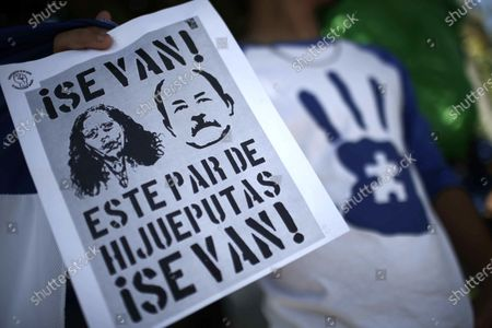 A protester shows a poster with the images of Nicaraguan President Daniel Ortega and his wife and Vice President of the country, Rosario Murillo, during a demonstration of Nicaraguans living in Costa Rica who reject their country's government, outside the facilities of the Organization of American States (OAS), in San Jose, Costa Rica, 20 October 2020.