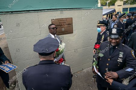 Stock Picture of Father of Randolph Holder (C) attends bridge name dedication and plaque installation in memory of his son in Harlem. Pedestrian footbridge over Franklin D. Roosevelt Drive at 120th Street where officer Holder was killed in 2015 connects Harlem streets and public bike and walkway along Harlem river. Randolph Holder was posthumously promoted from the rank of officer to the rank of Detective. Detective Randolph Holder was shot and killed while pursuing an armed male subject.