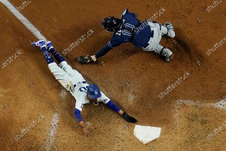 Los Angeles Dodgers' Mookie Betts scores past Tampa Bay Rays catcher Mike Zunino on a fielders choice by Max Muncy during the fifth inning in Game 1 of the baseball World Series, in Arlington, Texas