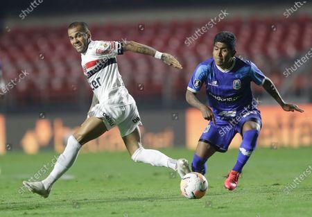 Daniel Alves of Brazil's Sao Paulo, left, and Pablo Labrin of Peru's Binacional battle for the ball during a Copa Libertadores soccer match at the Morumbi stadium in Sao Paulo, Brazil