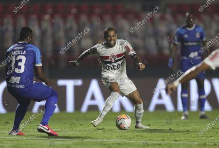 Stock Image of Daniel Alves of Brazil's Sao Paulo, center, controls the ball during a Copa Libertadores soccer match against Peru's Binacional at the Morumbi stadium in Sao Paulo, Brazil