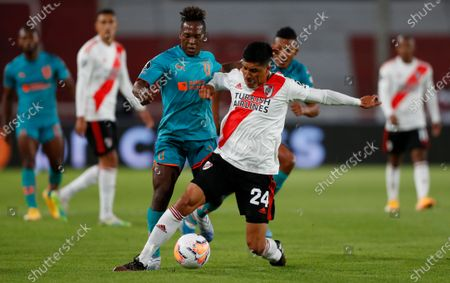 Stock Image of Jhojan Julio of Ecuador's Liga Deportiva Universitaria, left, and Enzo Perez of Argentina's River Plate battle for the ball during a Copa Libertadores soccer match in Buenos Aires, Argentina