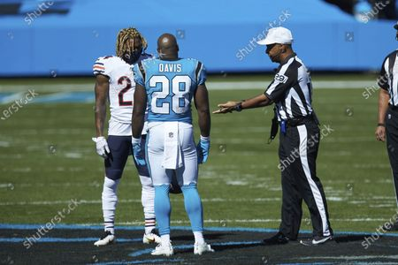 Referee Adrian Hall (29) shows the coin to captains Buster Skrine (24) of the Chicago Bears and Mike Davis (28) of the Carolina Panthers during an NFL football game, in Charlotte, N.C