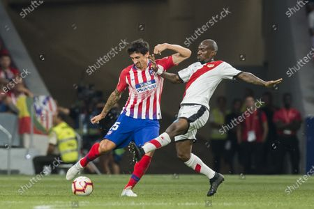 Stefan Savic (L) of Atletico de Madrid vies for the ball with Gael Kakuta of Rayo Vallecano during the La Liga 2018-19 match between Atletico de Madrid and Rayo Vallecano at Wanda Metropolitano