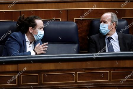Spanish Second Deputy Prime Minister Pablo Iglesias chats with Justice Minister, Juan Carlos Campo (R), as they attend the debate on a non-confidence voteagainst the government's coronavirus policy, issued by far-right party Vox, at Congress of Deputies in Madrid, Spain, 21 October 2020.