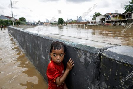 YEARENDER 2020  CLIMATE CHANGE   A boy stands next to a wall at a flooded road in Jakarta, Indonesia, 02 January 2020. Overnight heavy rains triggered widespread flooding in Jakarta and surrounding areas, killing at least 21 people.