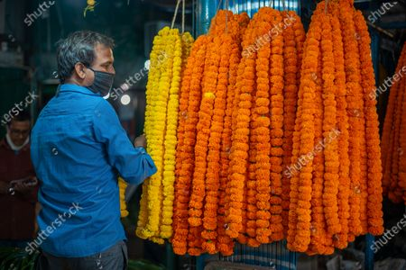 Stock Photo of Customer looking at hanging flowers in flower market. A wholesale flower market in New Delhi. Flowers are important in Hindu festivals for decoration and offering it to dieties. Covid-19 has a major impact on markets this year. Apparently, less footfall during festive season indicates low demand and economic downfall.
