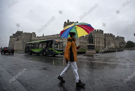 A man shelterers underneath an umbrella while walking through the town of Windsor in Berkshire as large parts of the UK are hit by heavy rain..