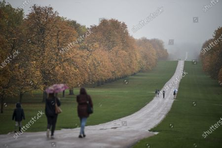 Members of the public shelter underneath umbrellas, amongst autumnal colours, on the Long Walk in Windsor, Berkshire.