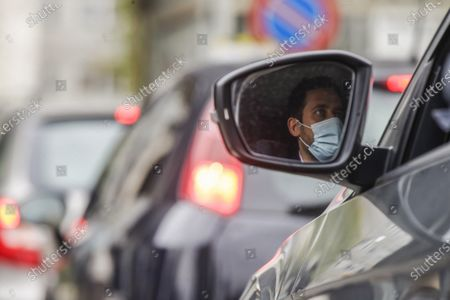 Cars line up at a drive through as people wait to get tested for COVID-19 at the San Carlo Borromeo hospital, in Milan, Italy
