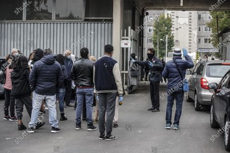 People line up to get tested for COVID-19 and argue with a guard outside the San Carlo Borromeo hospital, in Milan, Italy