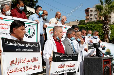 "Medical workers wear face masks and hold placards while staging a sit-in protest at the Unknown Soldier Square in Gaza City, . Arabic reads ""Makassed hospital is a national address for the Palestinian people."" ""We call on President Abu Mazen to intervene and bring us back to work."" Seven medical workers from the Gaza Strip said Wednesday an Israeli travel ban deprived them from getting to the east Jerusalem hospital where they worked for many years and the hospital eventually fired them"