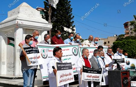 "Stock Image of Medical workers wear face masks and hold placards while staging a sit-in protest at the Unknown Soldier Square in Gaza City, . Arabic reads: ""Makassed Hospital is a national address for the Palestinian people."" ""We call on President Abu Mazen to intervene and bring us back to work."" Seven medical workers from the Gaza Strip said Wednesday an Israeli travel ban deprived them from getting to the east Jerusalem hospital where they worked for many years and the hospital eventually fired them"