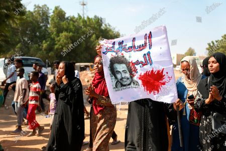 """Protester holds a banner which reads: """"The politicians who sold the blood, the martyr Abdul Salam Kesha,"""" at a demonstration, in Khartoum, Sudan, . Protesters have taken to the streets in the capital and across the country over dire living conditions and a deadly crackdown on demonstrators in the east earlier this month. Sudan is currently ruled by a joint civilian-military government, following the popular uprising that toppled longtime autocrat Omar al-Bashir last year"""