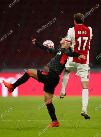 Liverpool's Takumi Minamino, left and Ajax's Daley Blind, right fight for the ball during the group D Champions League soccer match between Ajax and Liverpool at the Johan Cruyff ArenA in Amsterdam, Netherlands